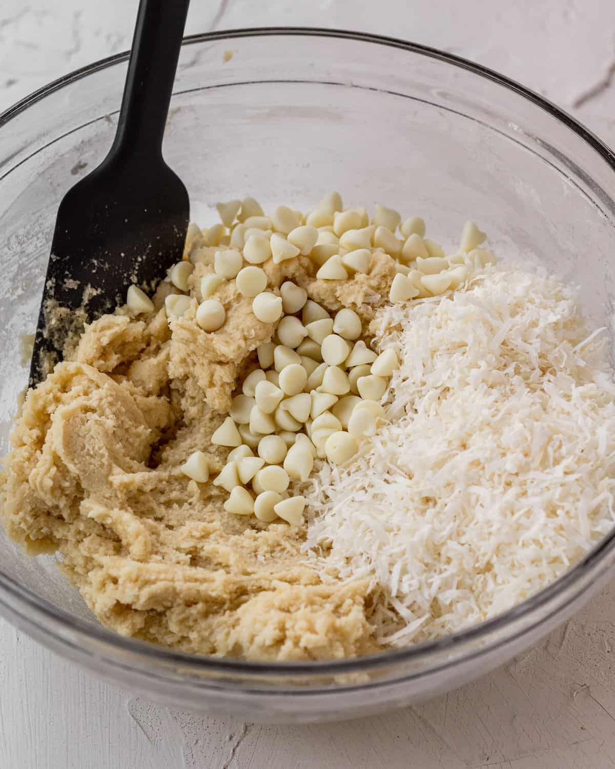 dough with coconut and white chocolate chips being mixed in