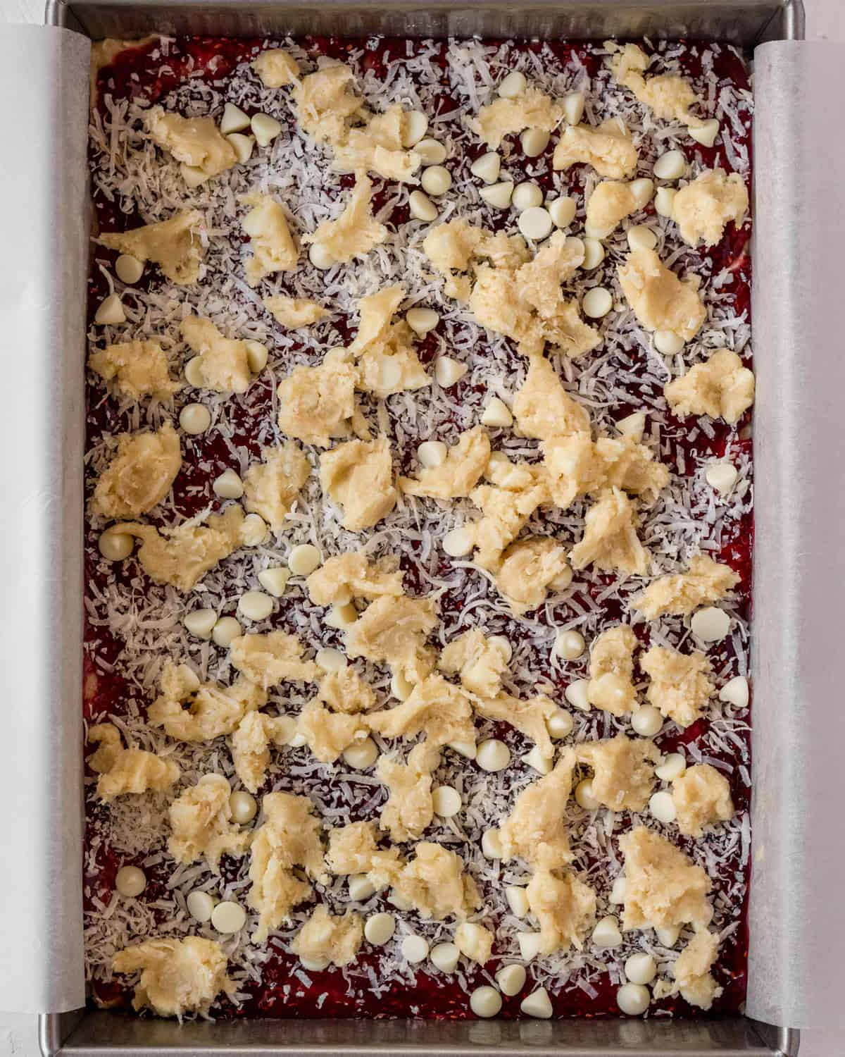 finished bars before baking in the oven with layers of raspberry, coconut, white chocolate, and more dough.