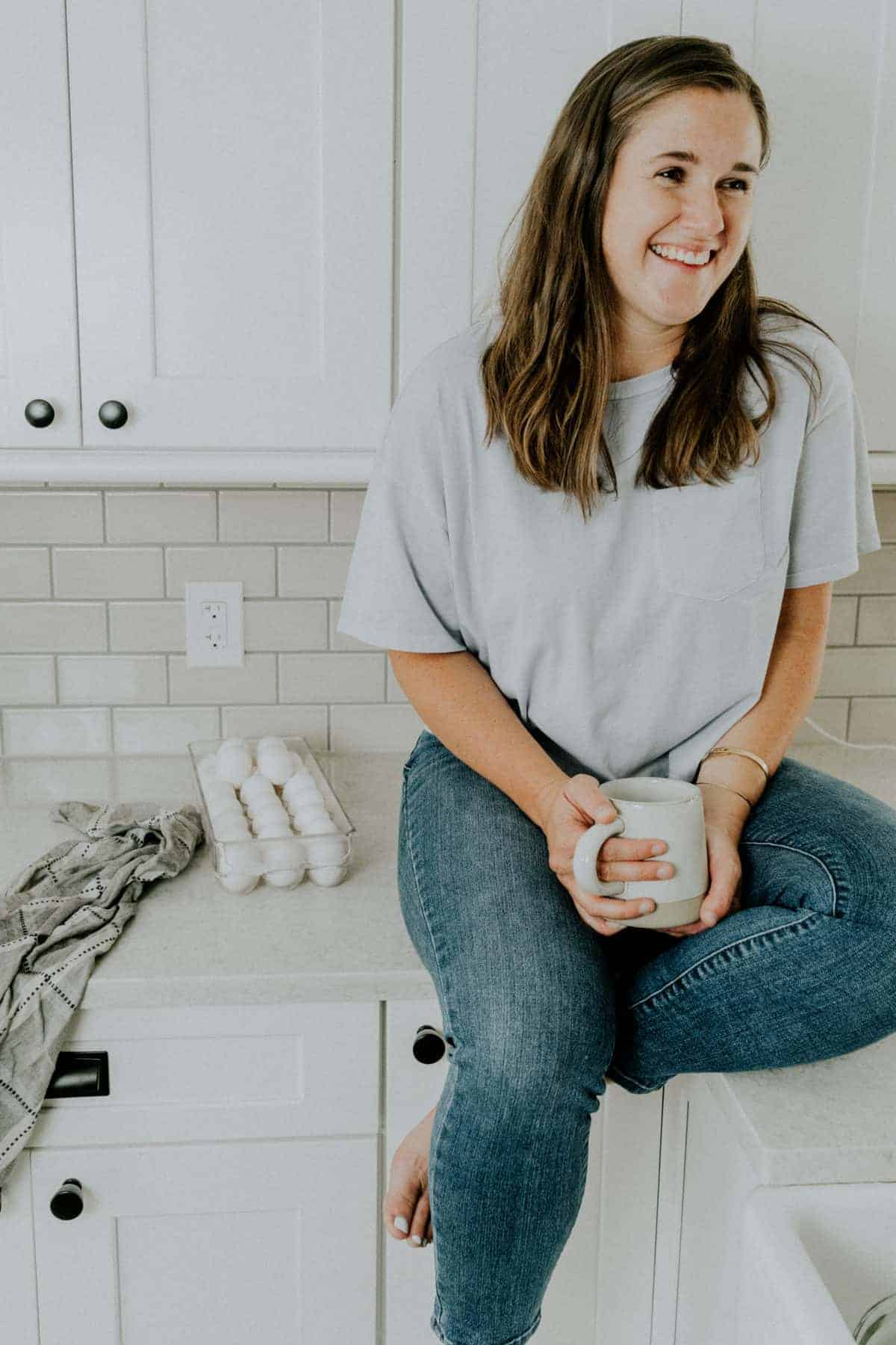 Kelly sitting on a counter with a coffee mug in hand and a tray of eggs next to her
