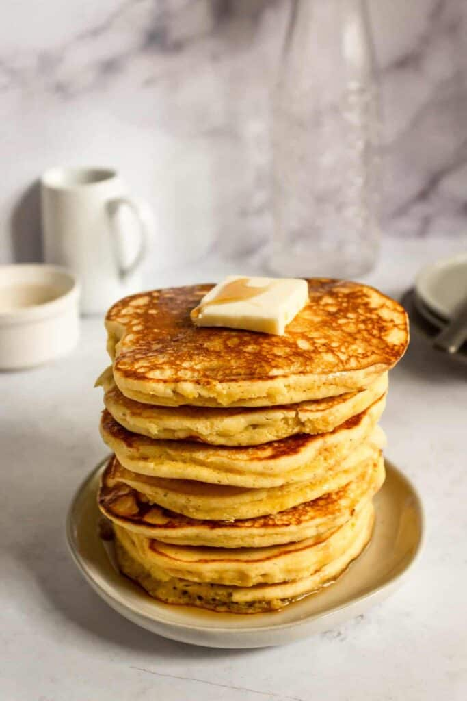 cornmeal pancakes in a stack with butter on top