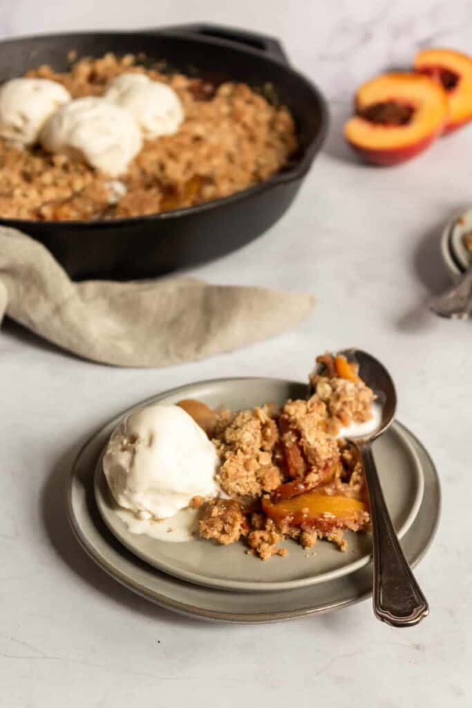 plate with serving of skillet peach crisp