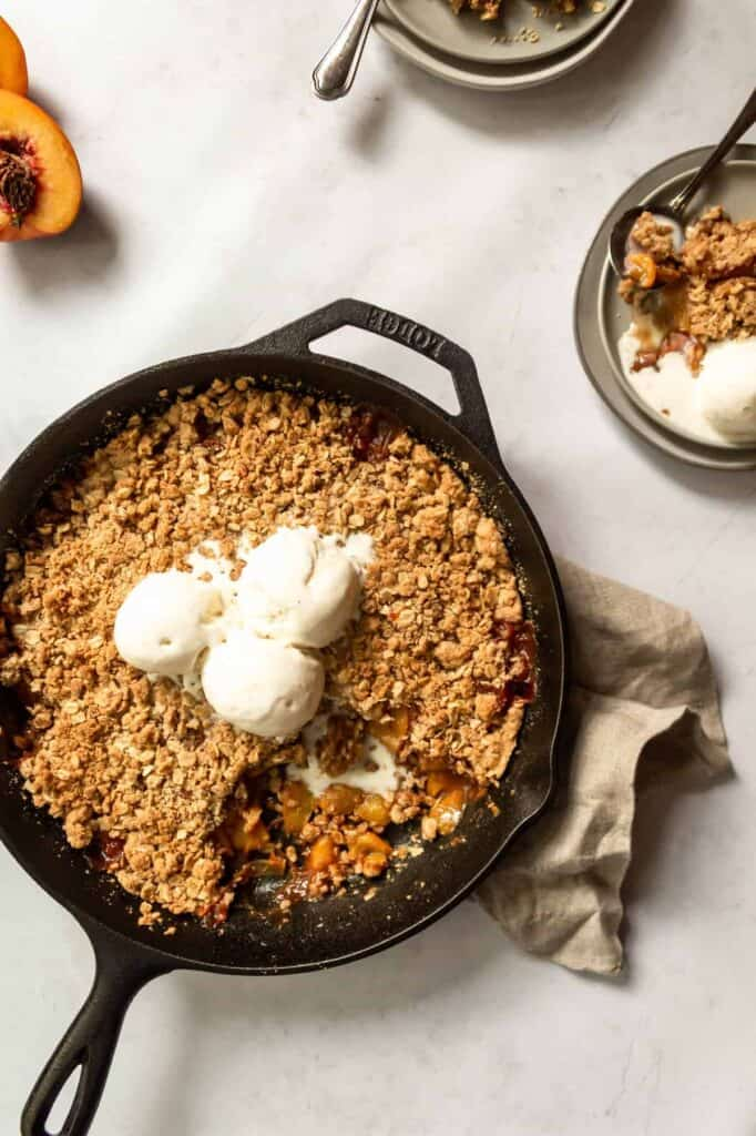 overhead view of skillet peach crisp and a serving on a plate