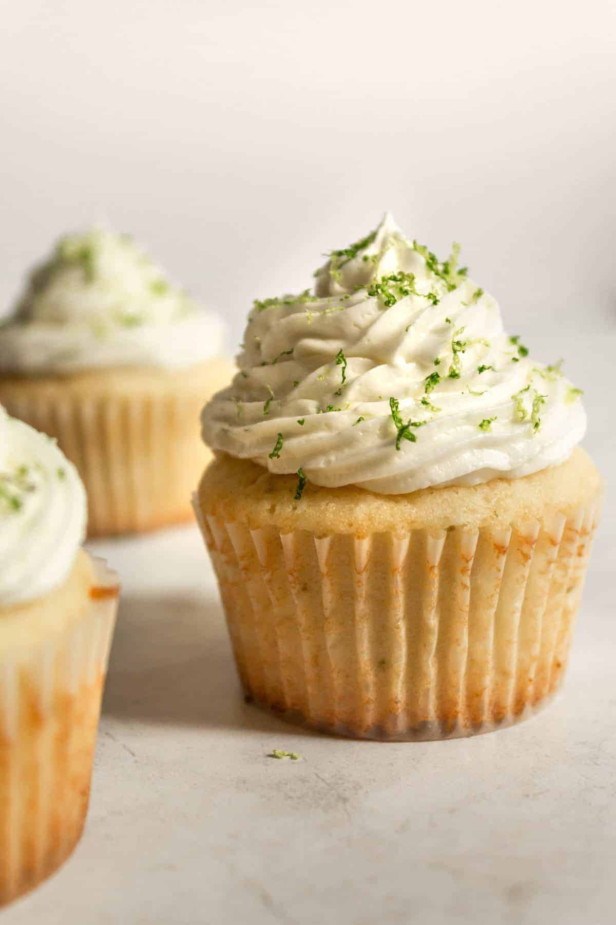 close up of a key lime cupcake with two off to the right of it.