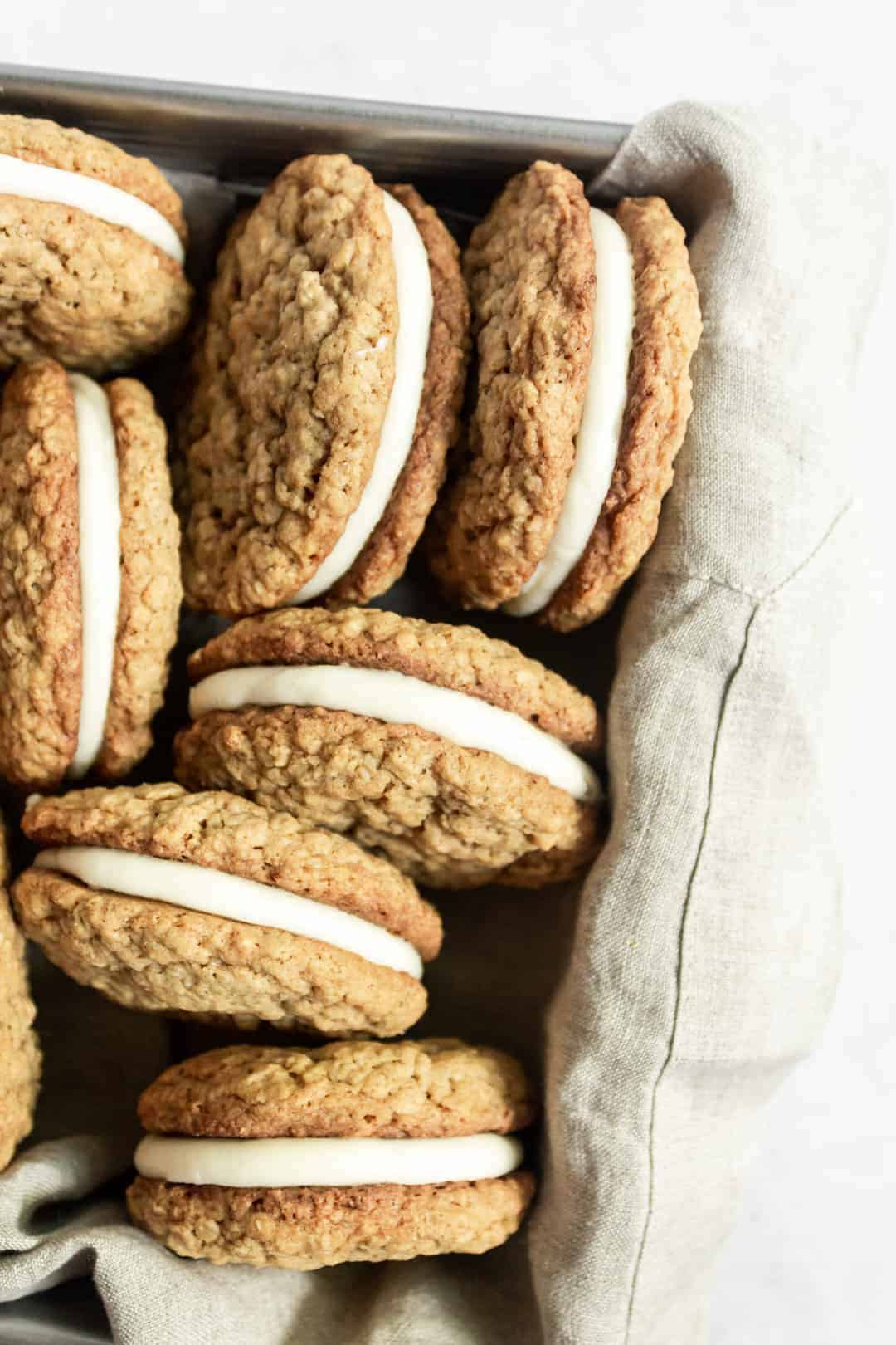 bunch of oatmeal creme pies in a cloth lined baking pan.