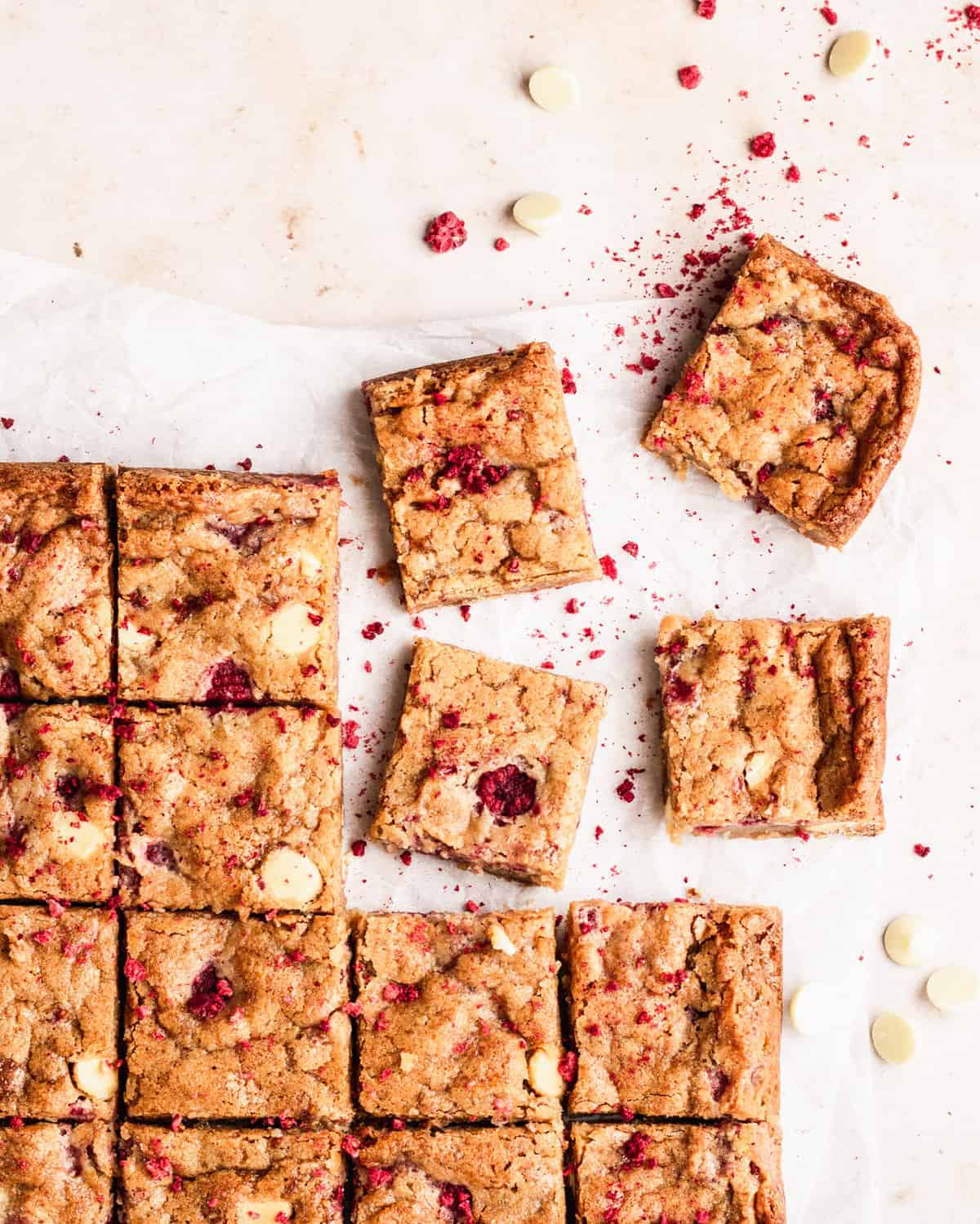 raspberry white chocolate blondies cut into squares and dusted with freeze-dried raspberries