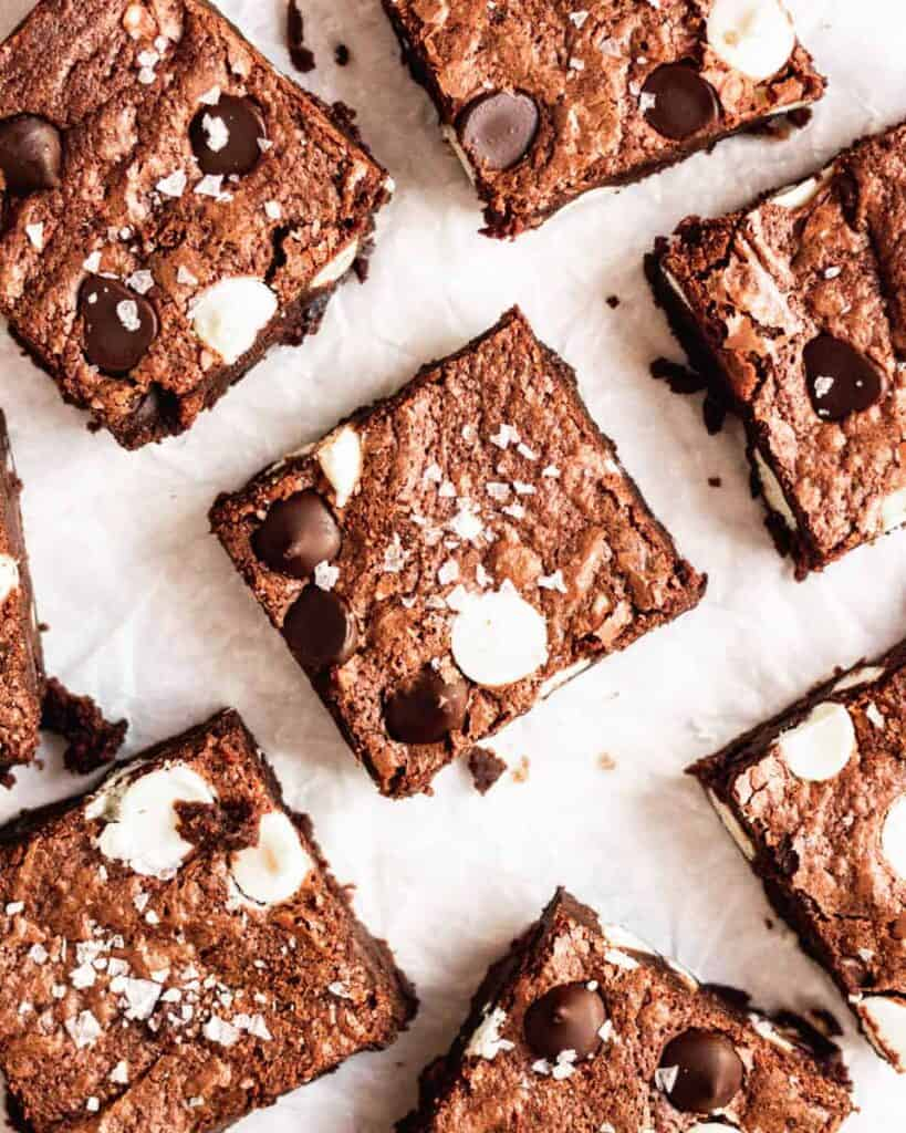 overhead view of baked triple chocolate brownies with flaky sea salt to finish.