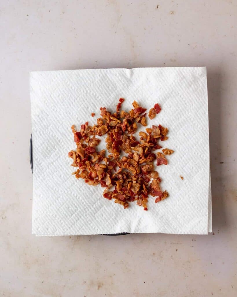 bacon bits that are done and draining on paper towel-lined plate