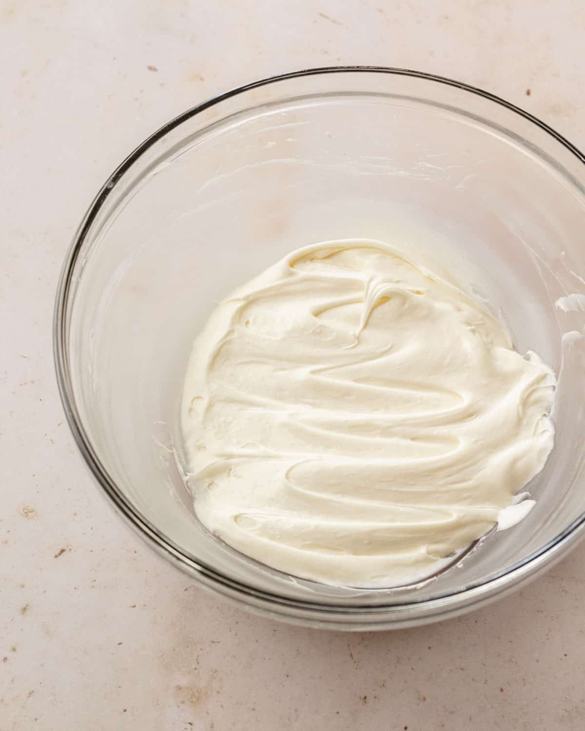 super smooth cream cheese icing in a bowl, ready to be piped onto brownies.