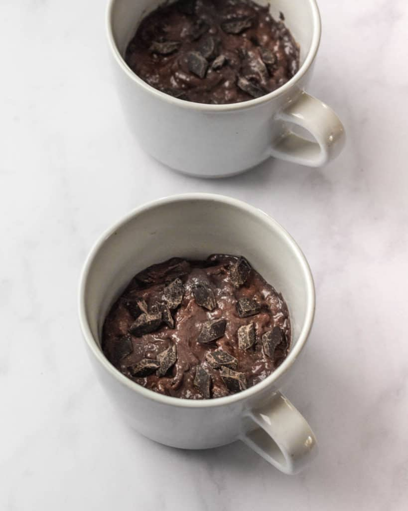 Un-baked banana bread batter in the mugs with chocolate chunks on top