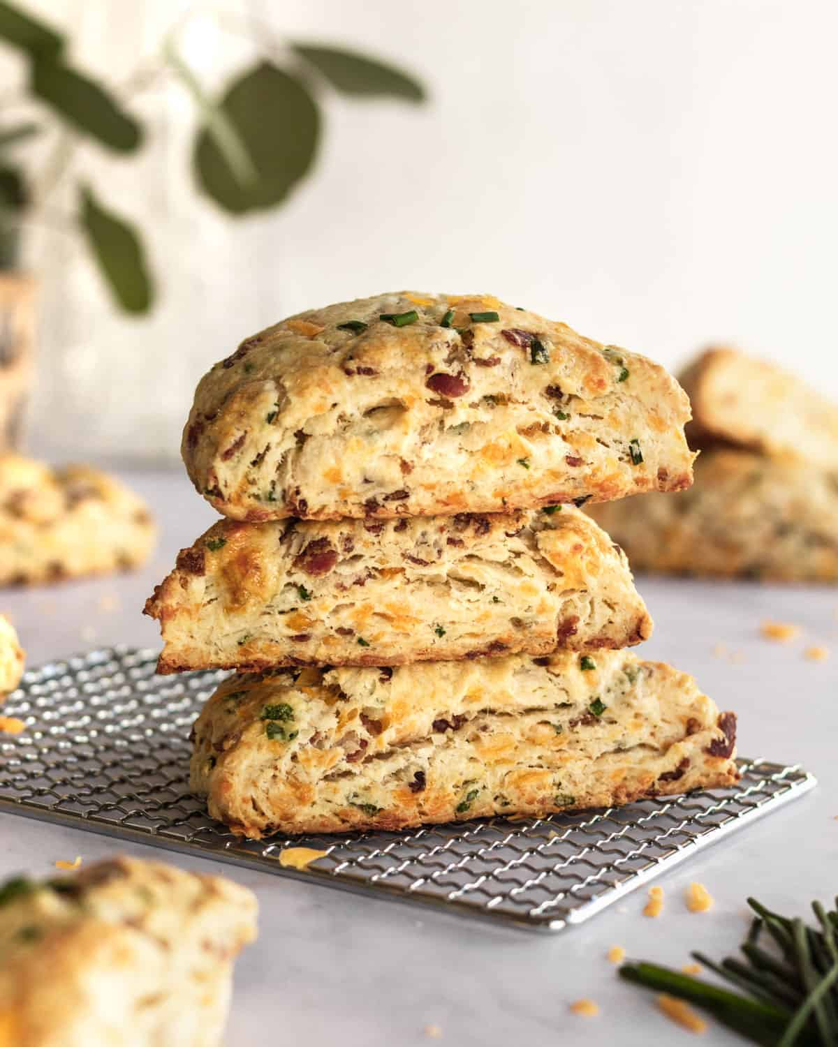 stack of 3 cheddar bacon chive scones on top of one another.