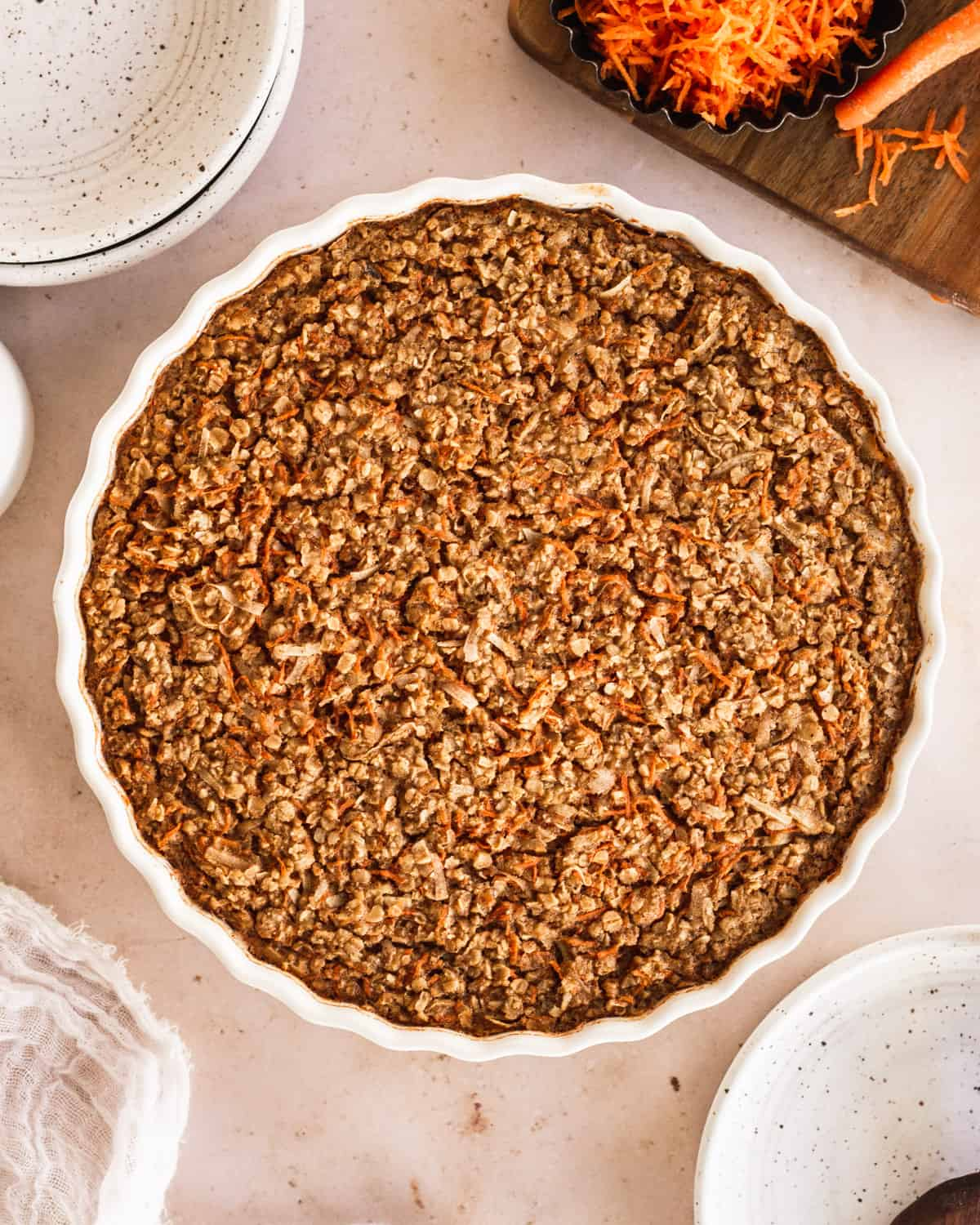 overhead view of baked oatmeal right out of the oven with shredded carrots on the side