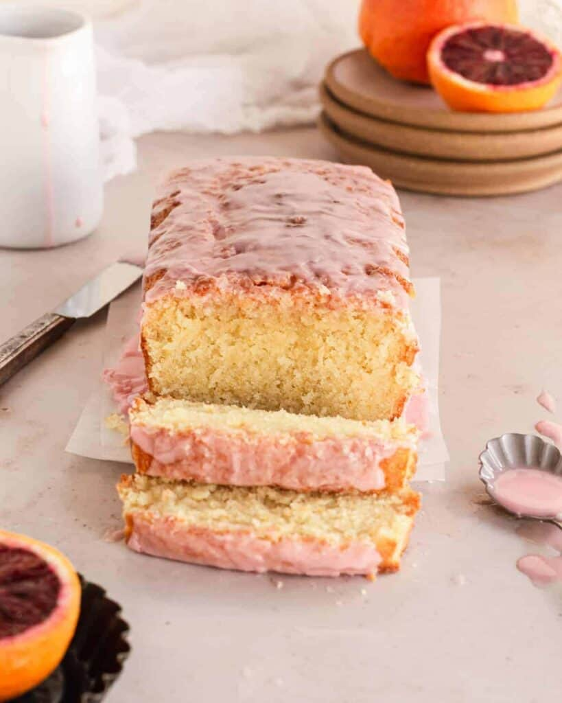 loaf of almond pound cake with two slices cut in front of it, plates stacked behind with blood oranges on top.