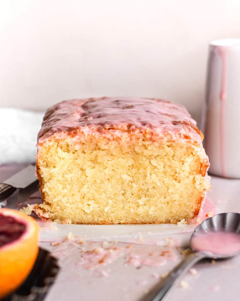 a close up of the inside of the almond pound cake, moist crumbs with pink glaze on top.