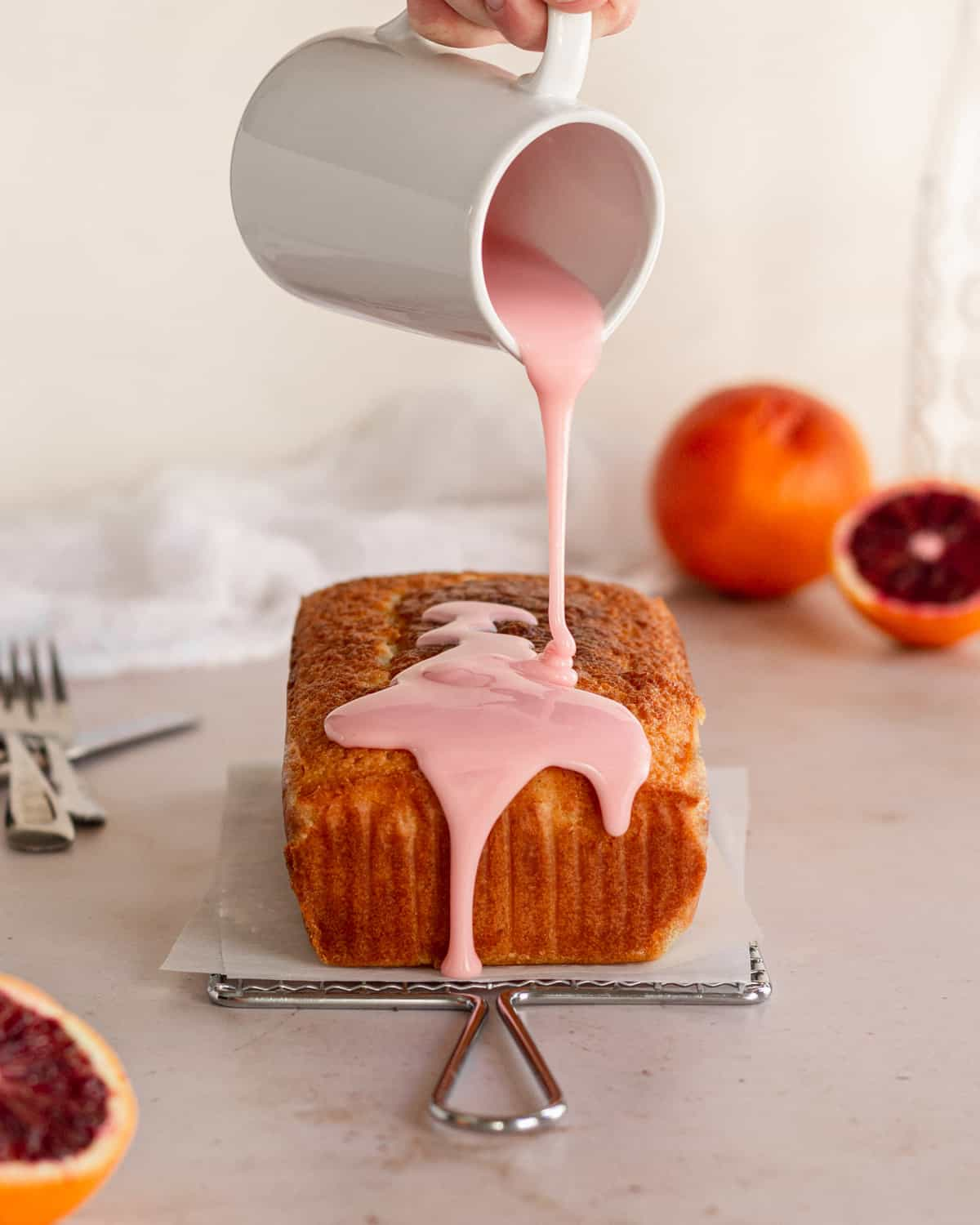 naked loaf cake with drizzle of pink blood orange icing being poured on top.
