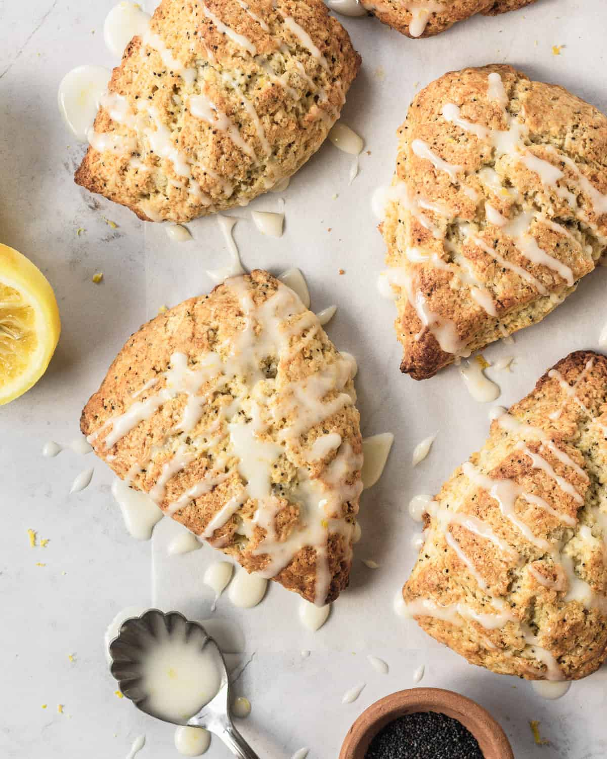 overhead view of lemon scones with glazed drizzled over top sitting on parchment paper with a lemon next to it.