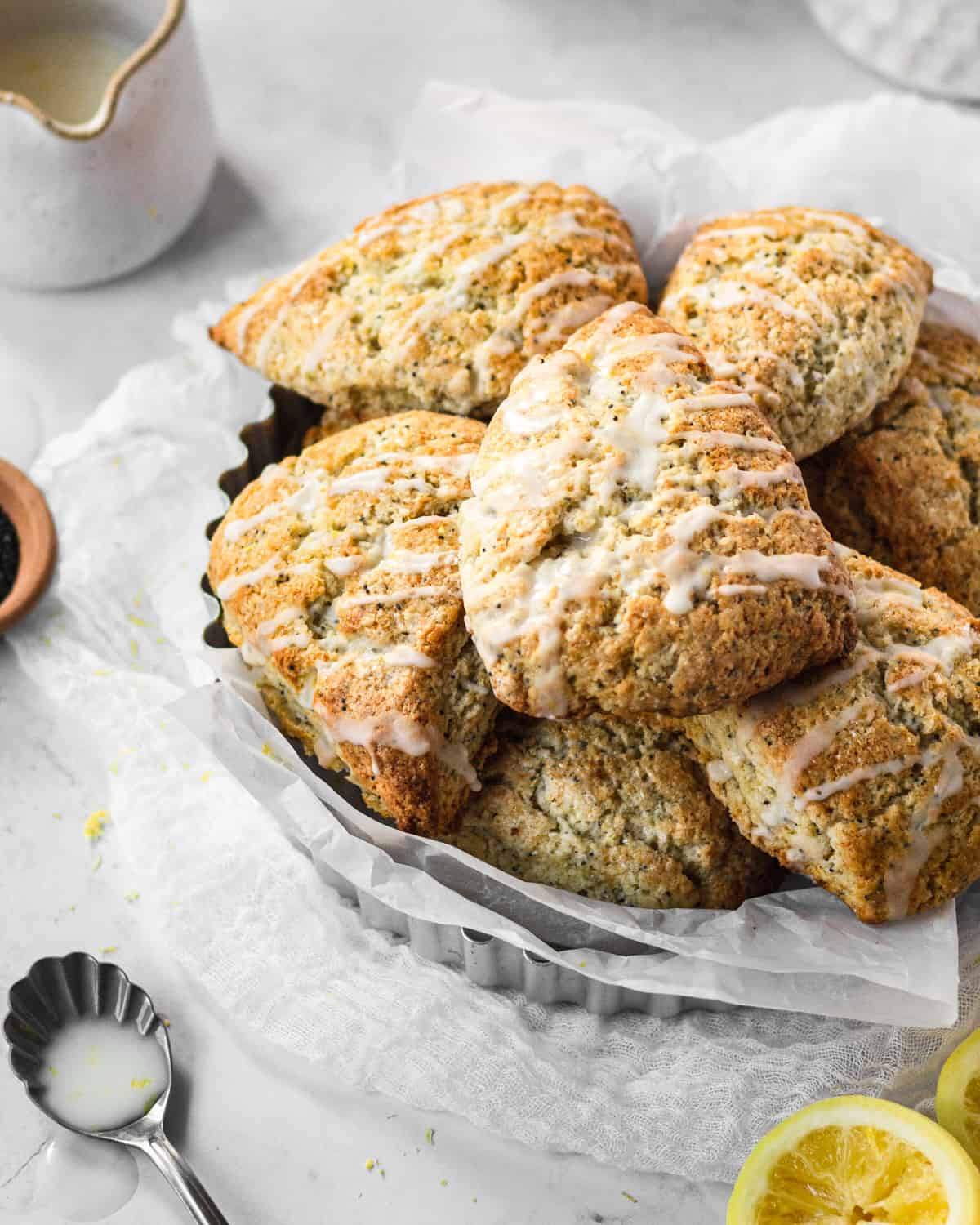 bowl of scones stacked on top of one another with glaze drizzled over top with a spoon of glaze sitting next to it.