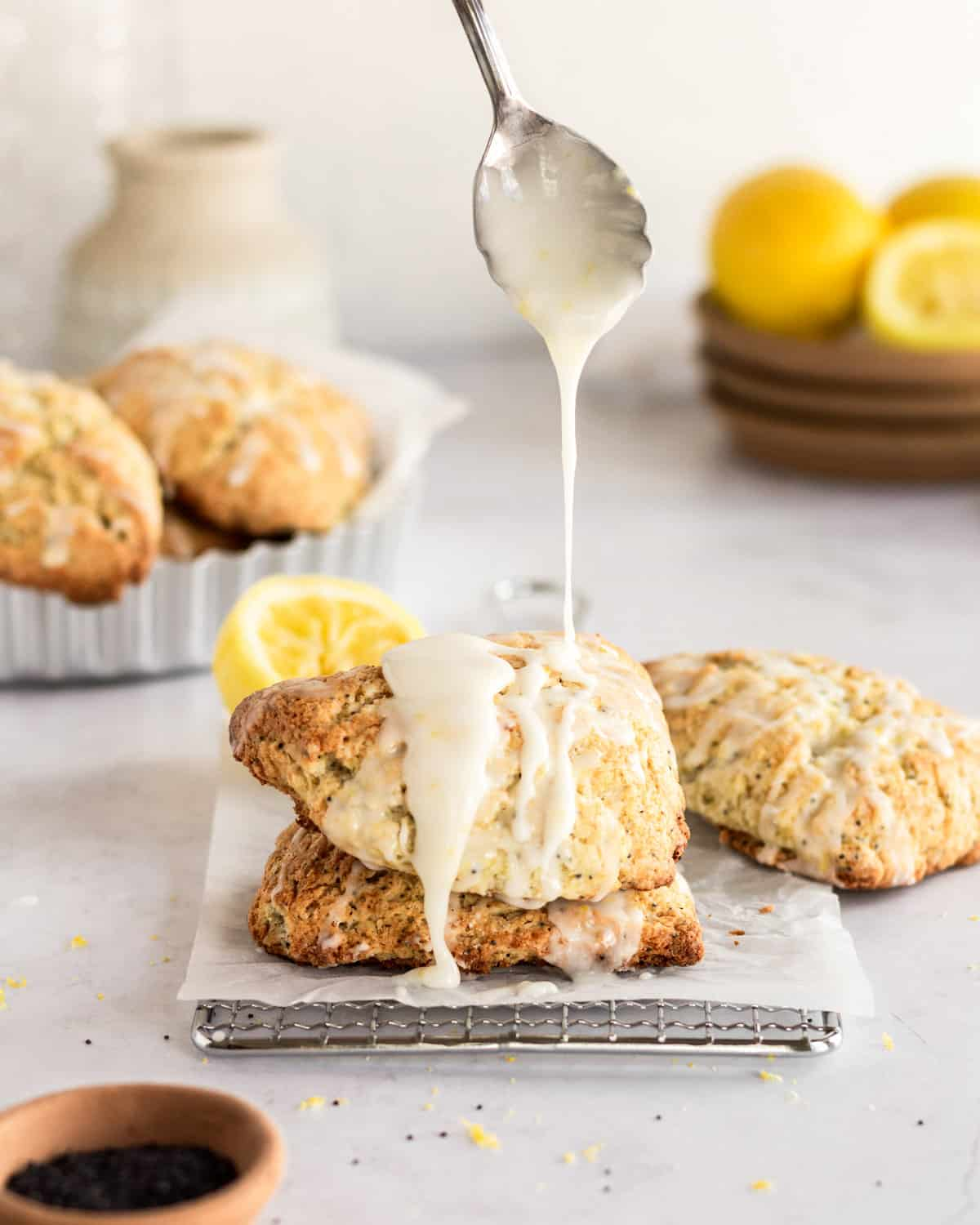 stack of scones with spoon over top drizzling lemon glaze onto scones. In the background there is a bowl of scones and a plate full of lemons.