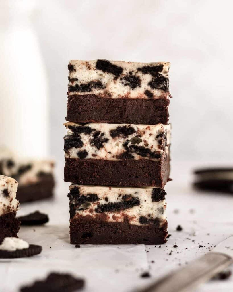 stack of 3 oreo cheesecake brownies on top of one another with other brownies surrounding it.