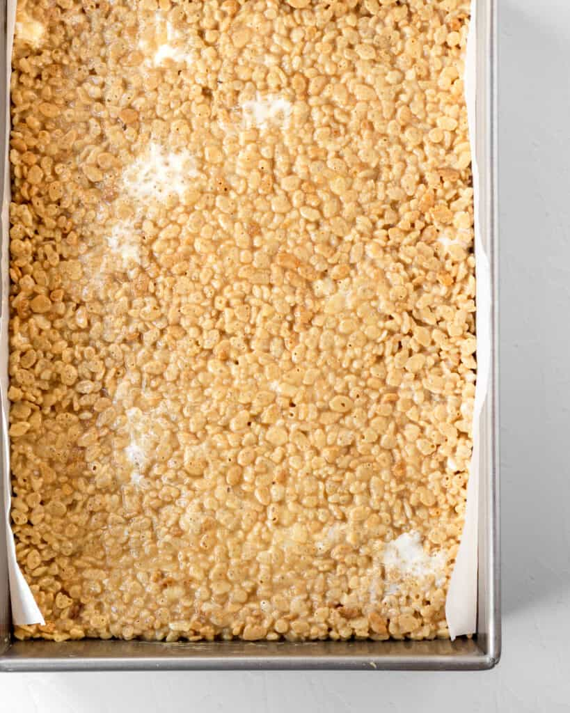 rice kripies treats pressed into a baking dish and cooling.