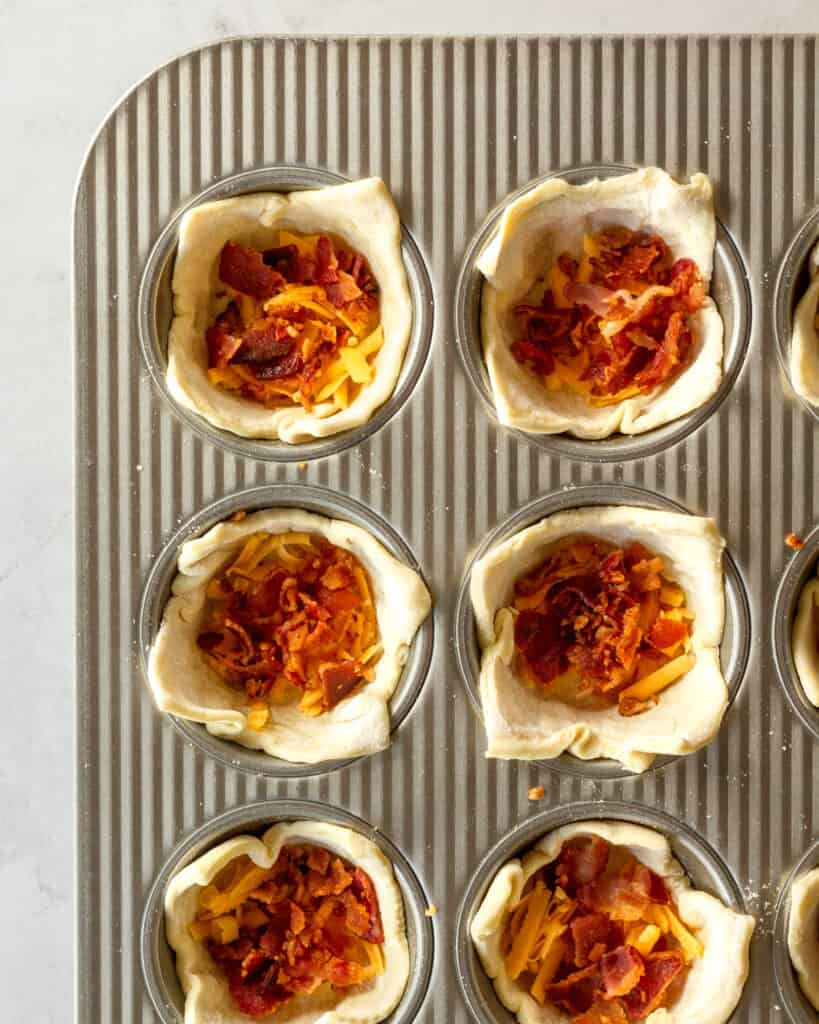 bacon and cheese added into the puff pastry breakfast cups