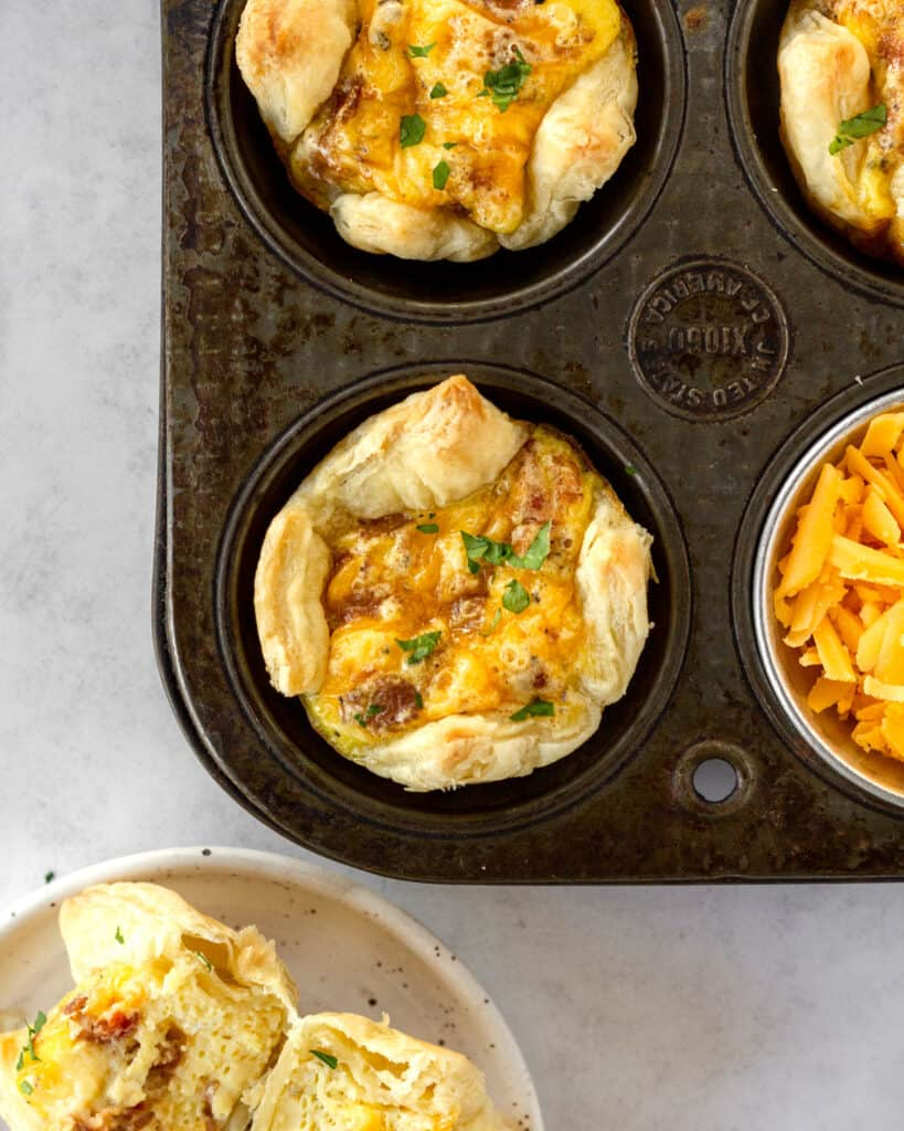 overhead view of puff pastry cups in a muffin tin with a cup of cheese next to it.