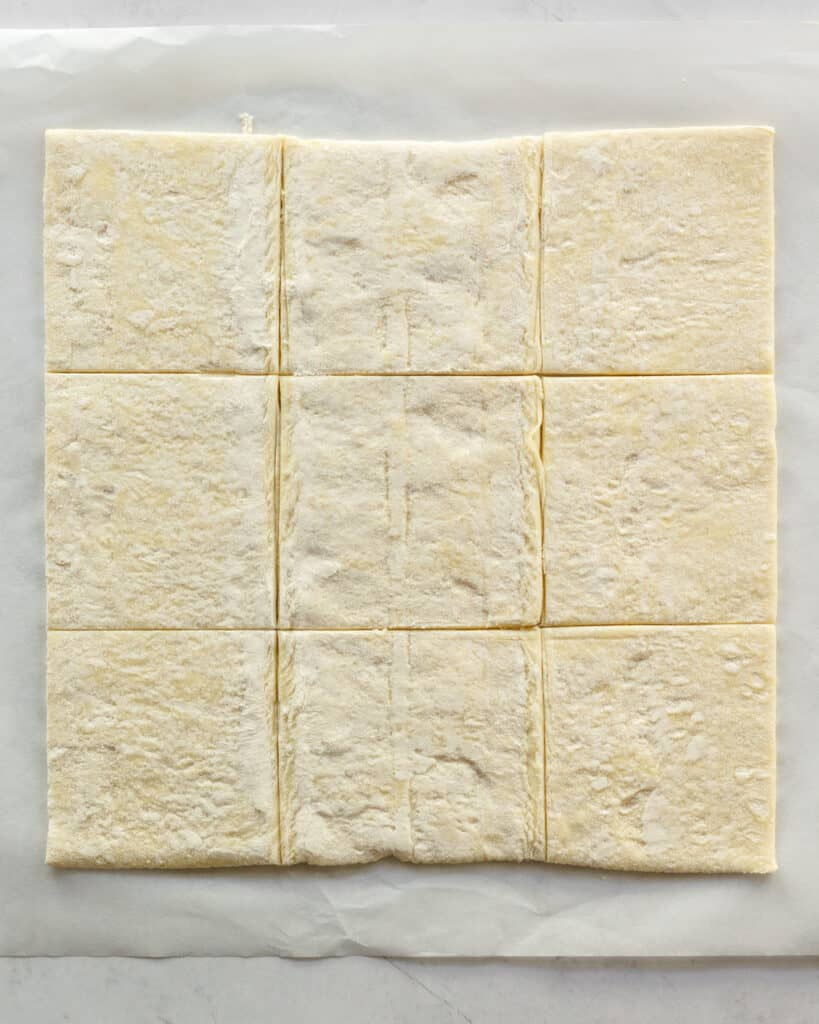Puff pastry sheet flattened out and cut into 9 squares.