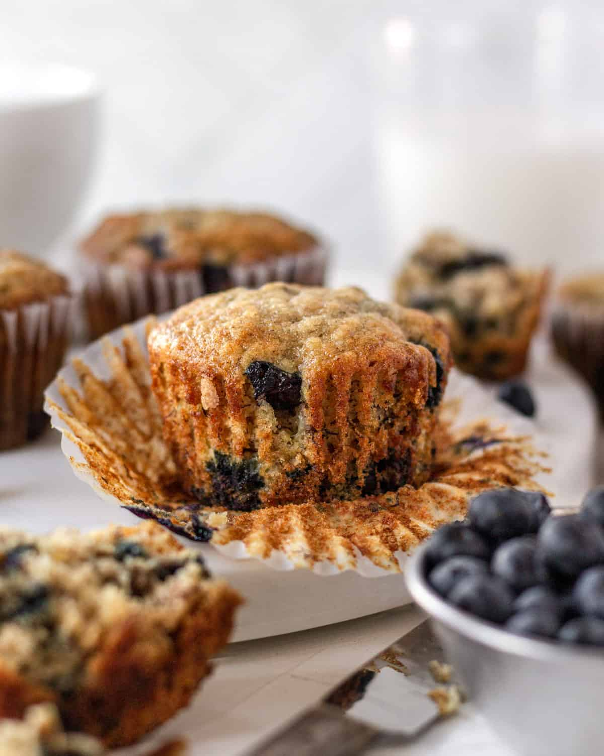 a banana blueberry muffin with the wrapper taken off on a platter with other muffins. a bowl of blueberries sitting next to it and a knife.