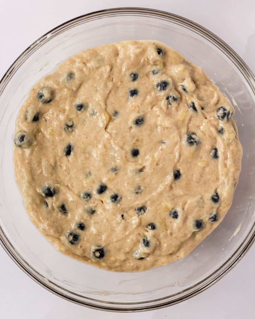 bowl of muffin batter with blueberries mixed in