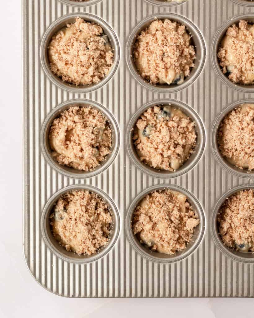 muffins scooped into muffin tin with streusel topping on top