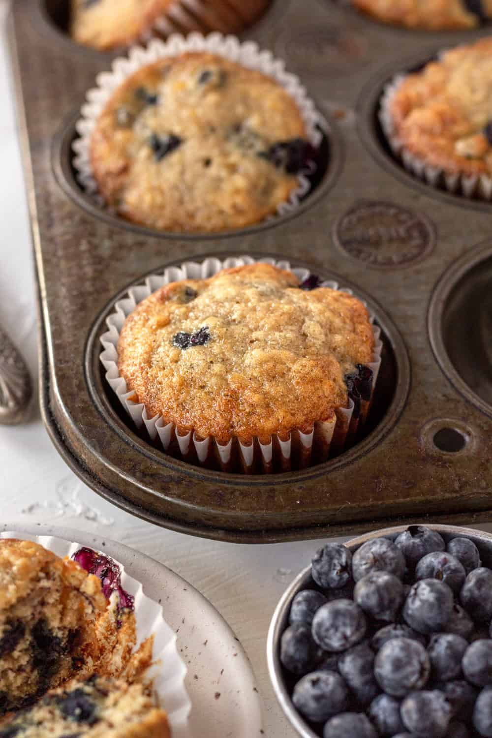 A muffin tin with baked banana blueberry muffins in it with a bowl of blueberries next to it.
