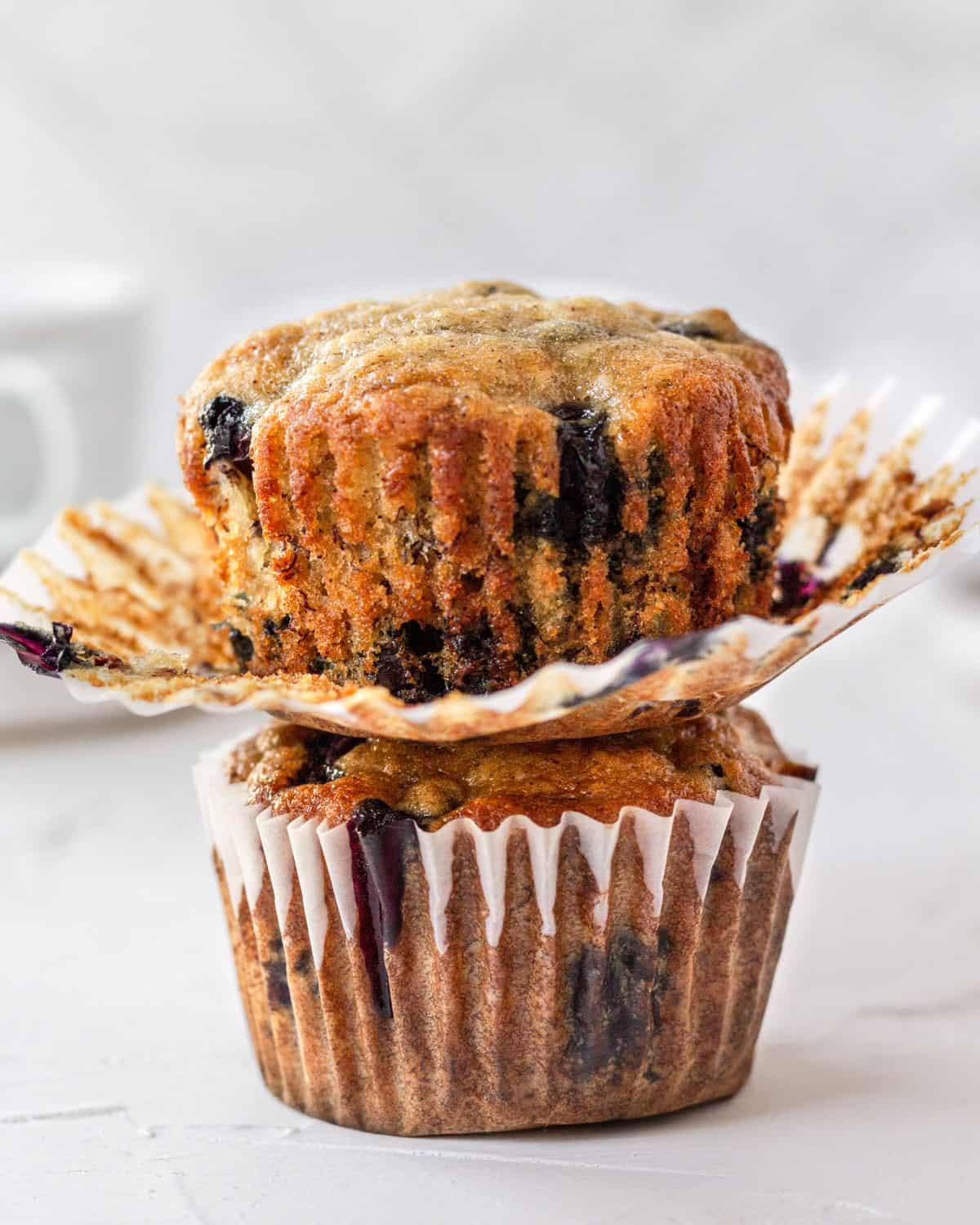 two banana blueberry muffins stacked on top of one another, top one has the wrapped pulled down.