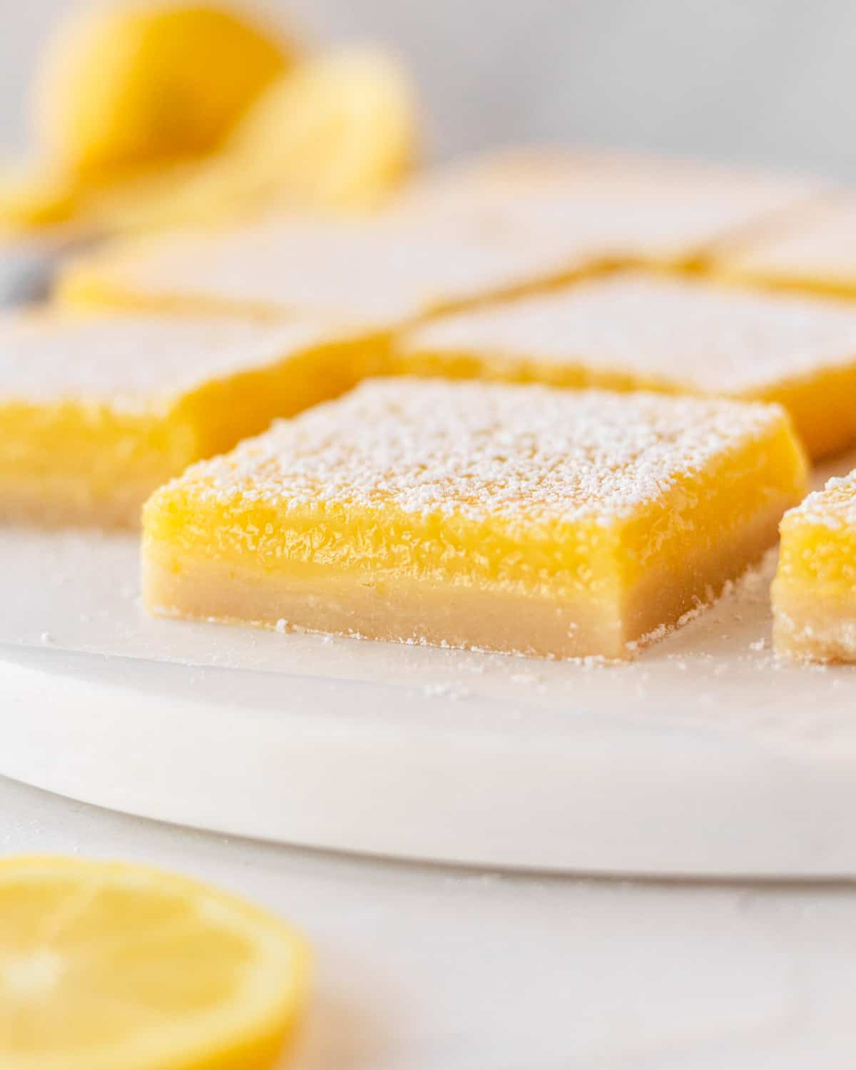 close up of lemon bar on a white platter with other lemon bars behind it