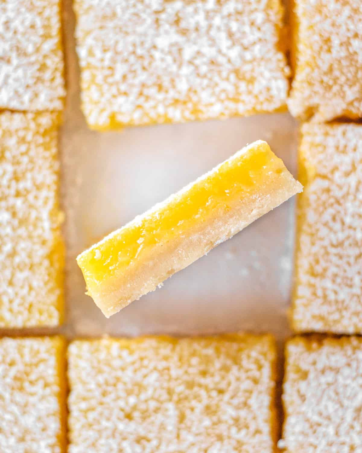 1 lemon bar turned up so you can see the layers of crust and lemon curd.