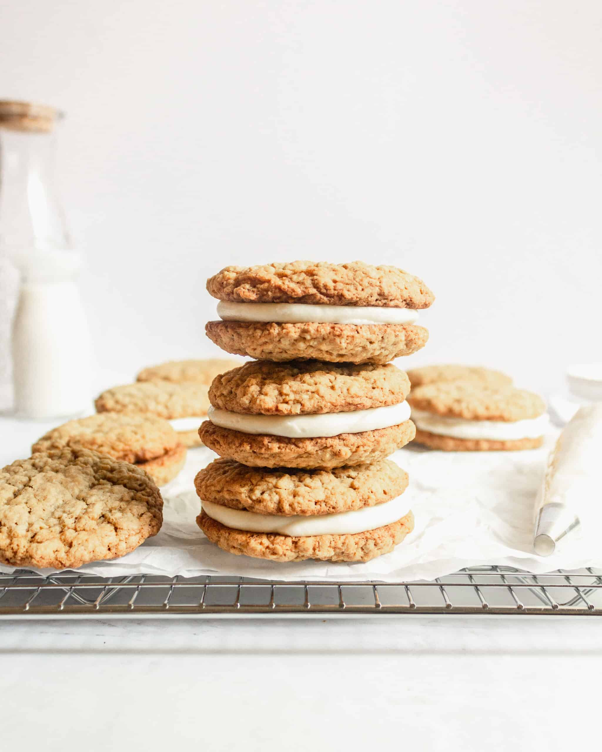 a stack of 3 oatmeal creme pies with cookies on the side and a piping bag of buttercream next to it.