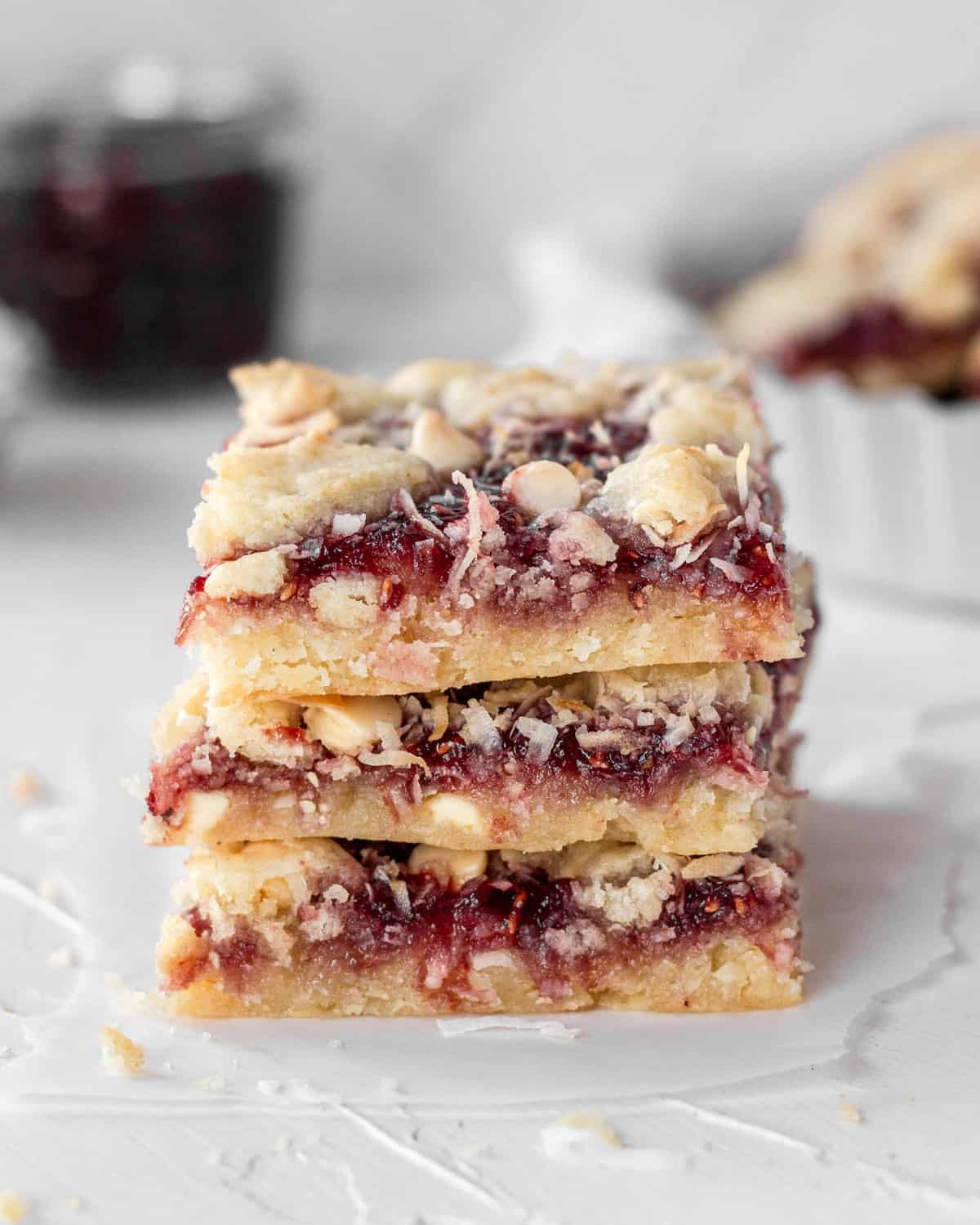 3 coconut raspberry bars stacked on top of one another with a bowl filled with bars and raspberry preserves in the background.