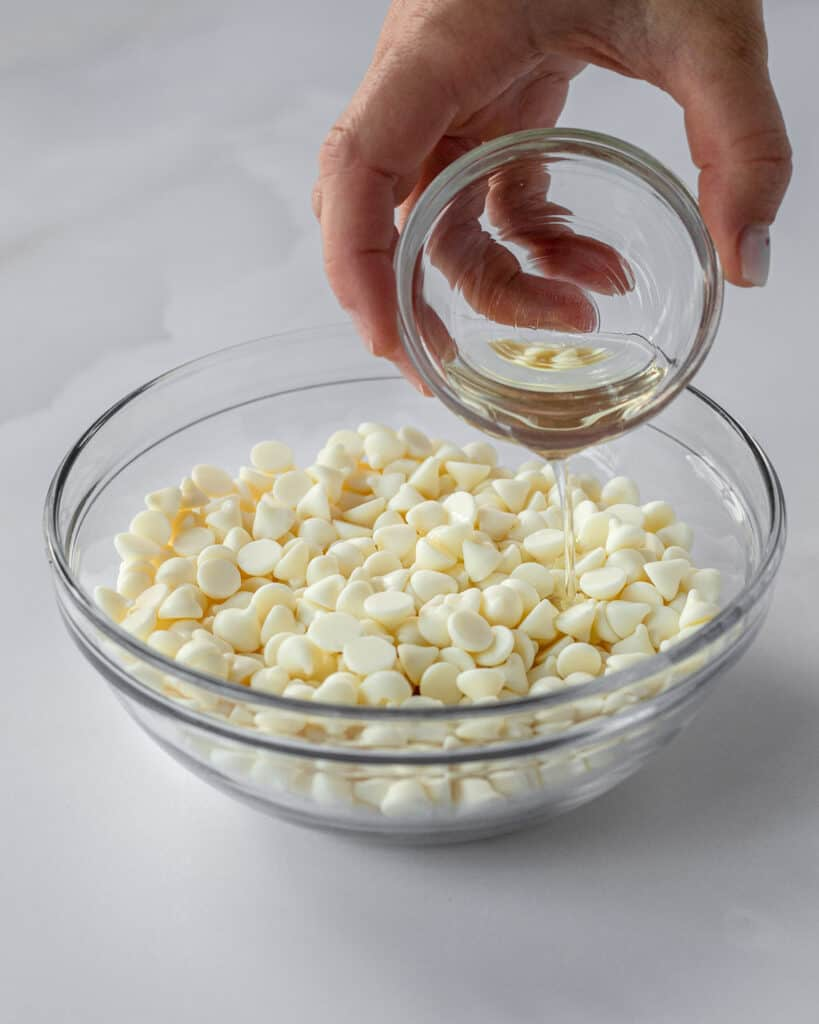 oil being poured into the white chocolate chips before microwaving