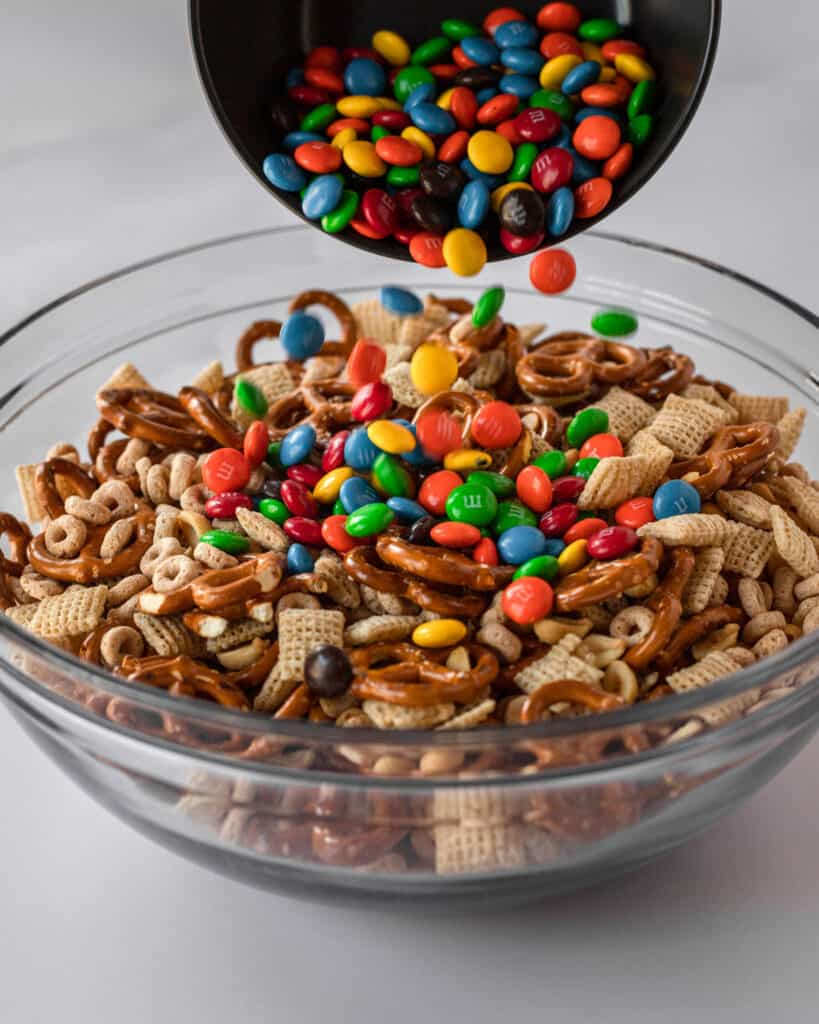 a bowl of m&ms being poured into the chex mix mixture.