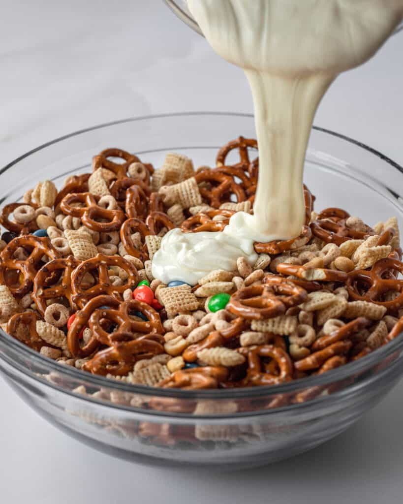 white chocolate being poured into the chex mix