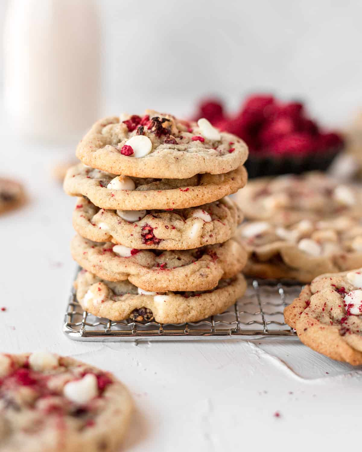 stack of 5 cookies on a wire cooling rack with cookies around and raspberries in the background