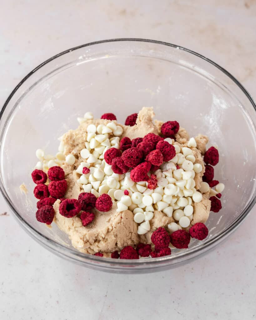 white chocolate chips and freeze-dried raspberries poured into the cookie dough