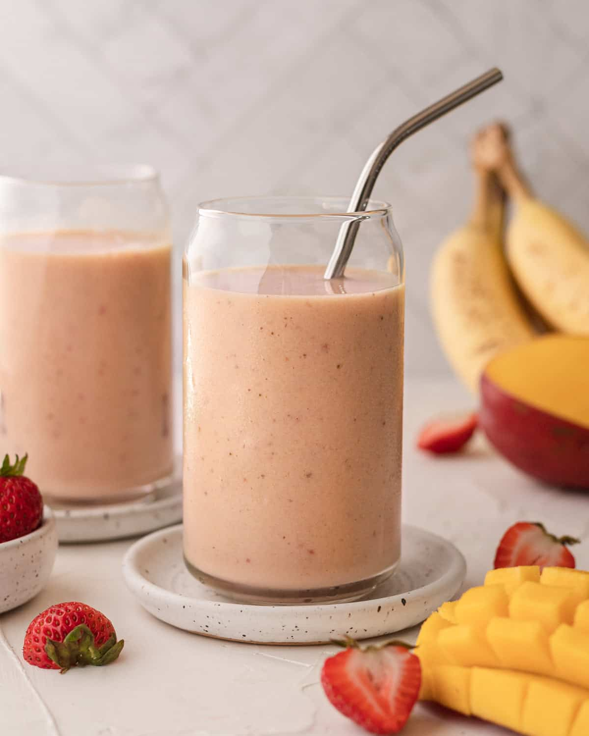 two clear glasses filled with mango strawberry banana smoothie with fruit spread out around it.