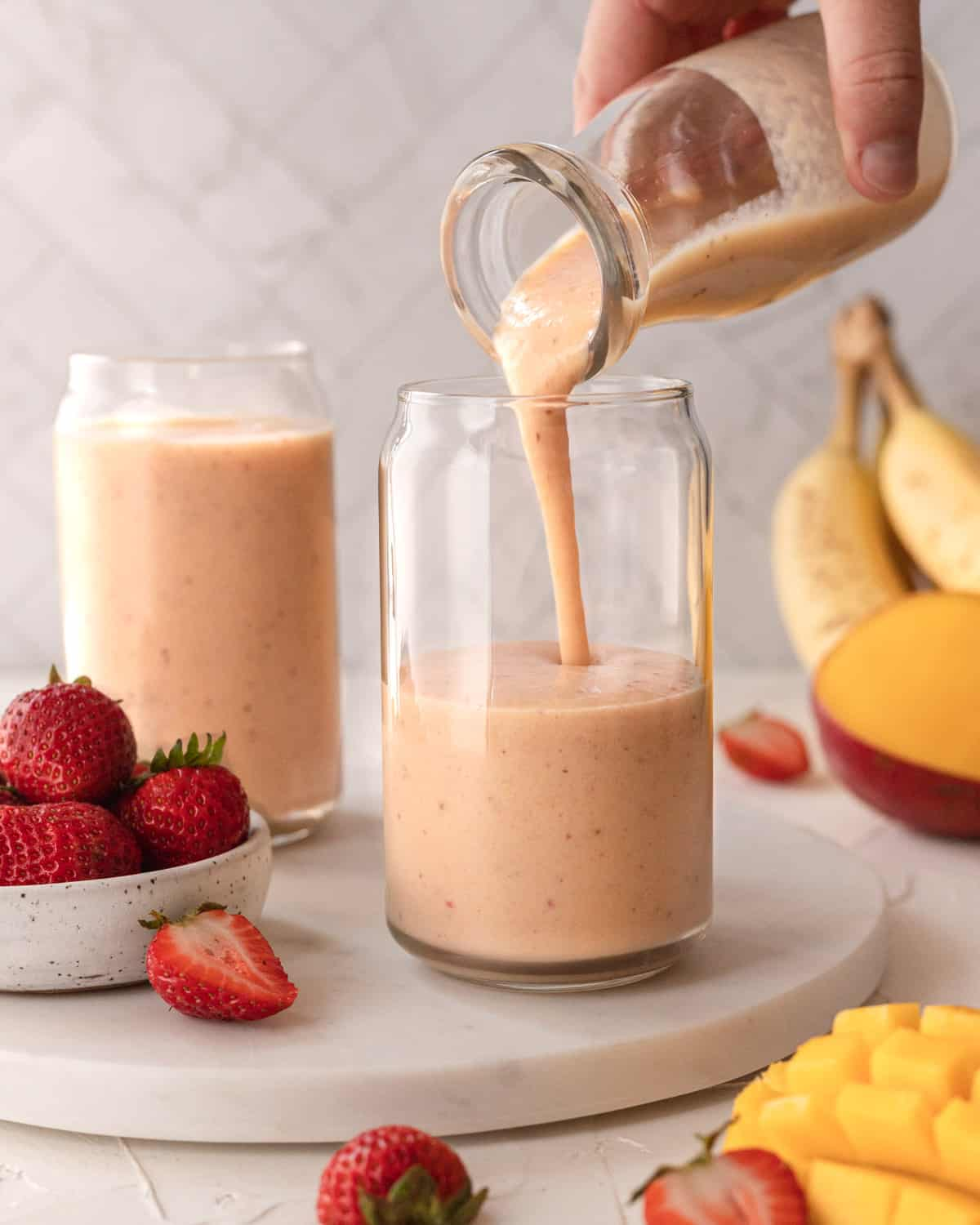 smoothie being poured into a clear glass on a white marble platter next to a bowl of strawberries.