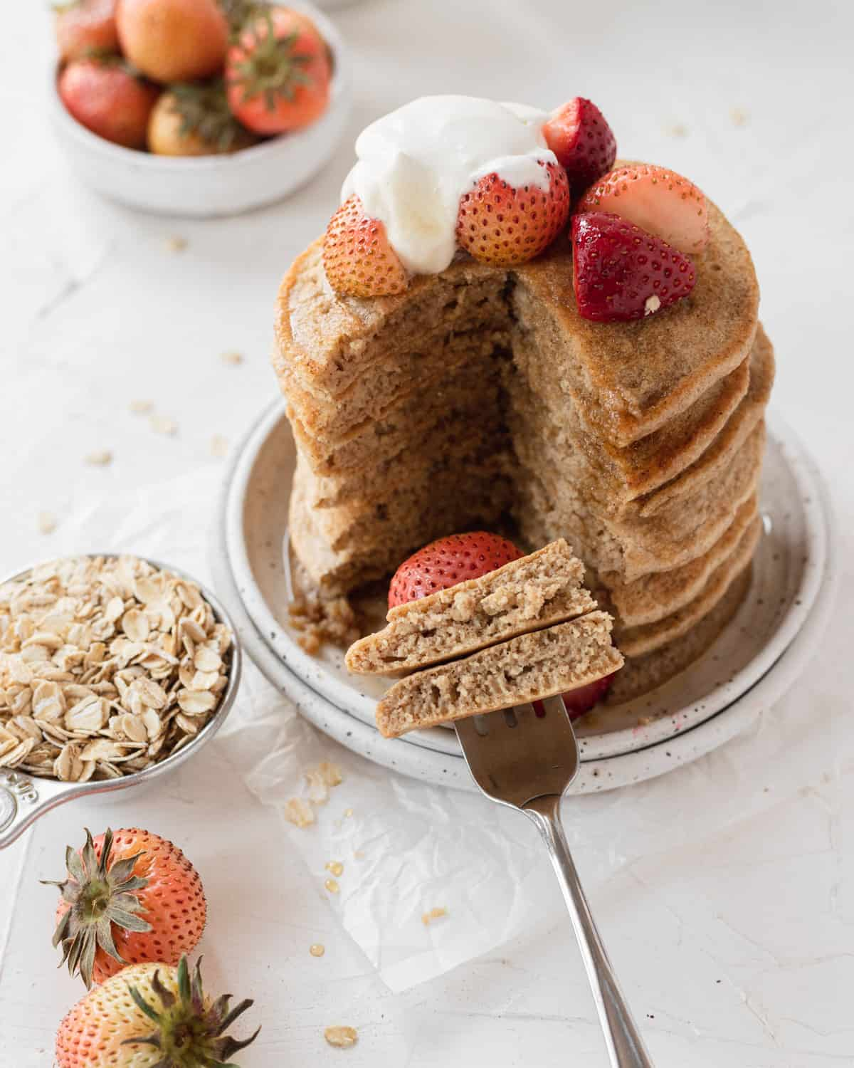 stack of pancake with a slice cut out of them, fork full of pancakes, next to a cup of oats.