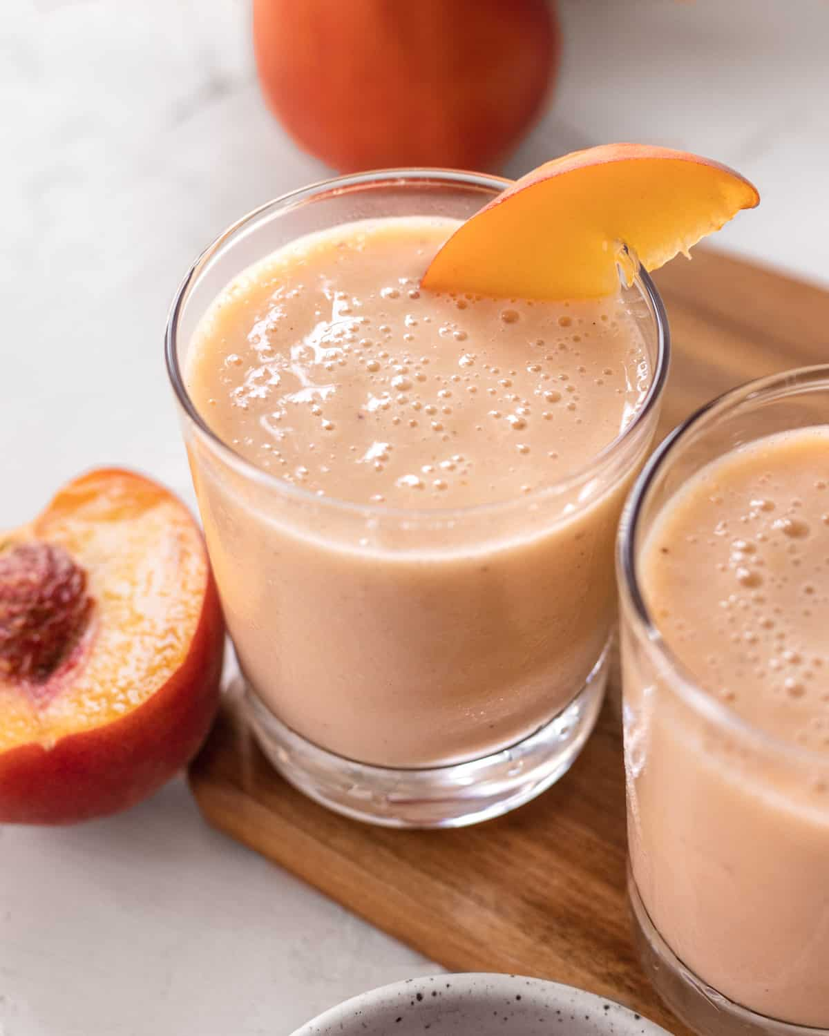 two glasses of banana peach smoothie with a cut open peach next to them.