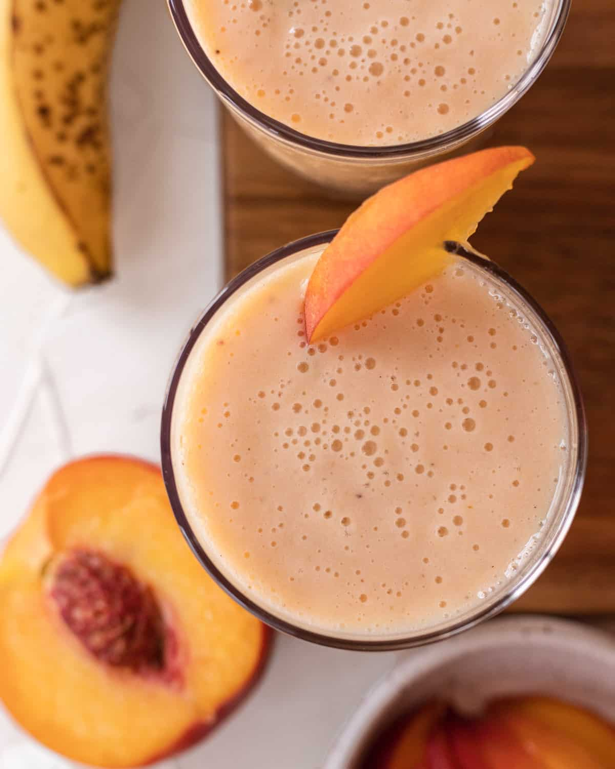 overhead view of two banana peach smoothies with peaches and a banana placed around it.