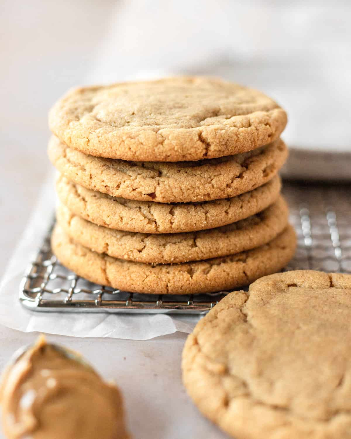 stack of 5 cookies with the 6th cookies down below near a spoonful of peanut butter
