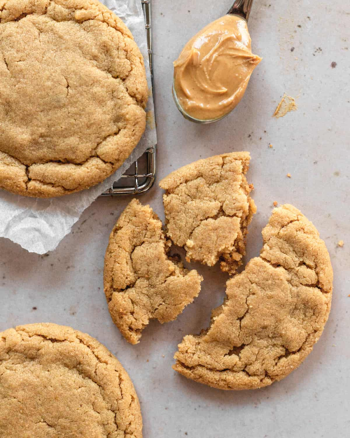 a cookie that is broken up with other cookies surrounding it and a spoonful of peanut butter.