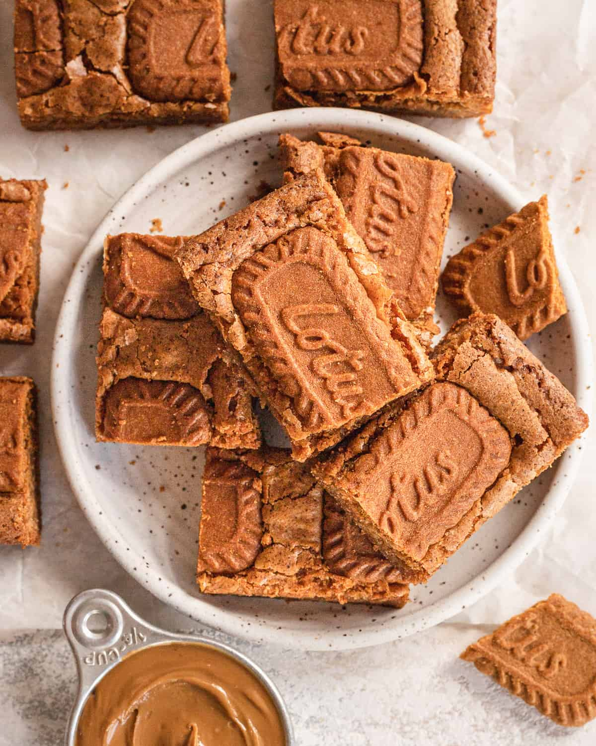 overhead view of biscoff blondies cut up into squares and placed on a plate with cookie butter spread next to it