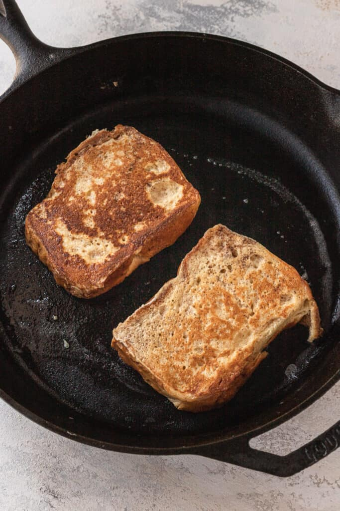 two slices of french toast cooking in a cast iron skillet