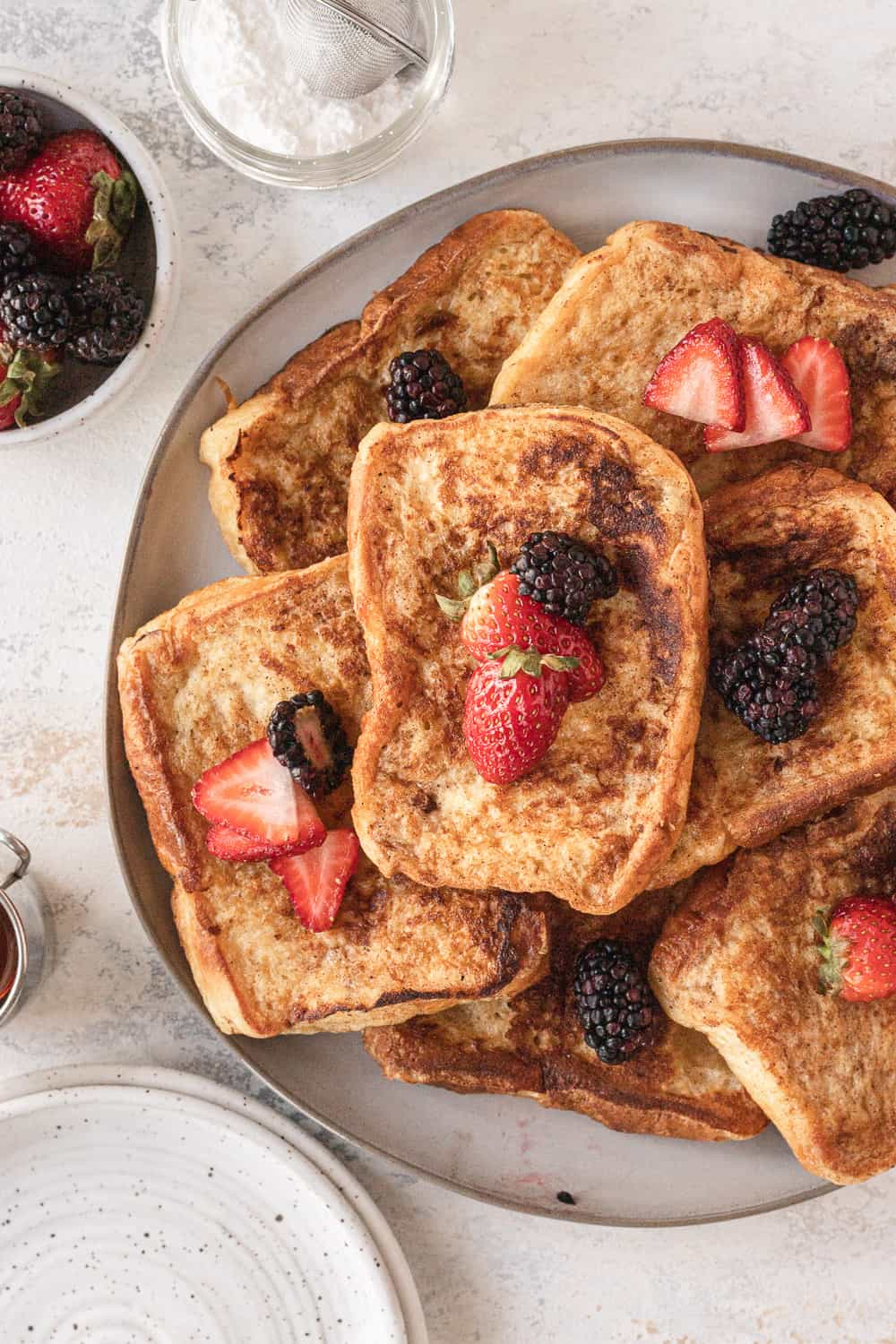 overhead view of a large platter of cooked french toast with powdered sugar, berries, and syrup on the side